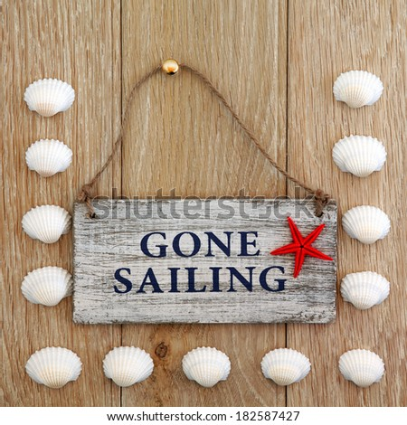 Sea shell abstract and gone sailing sign over old oak background. - stock photo