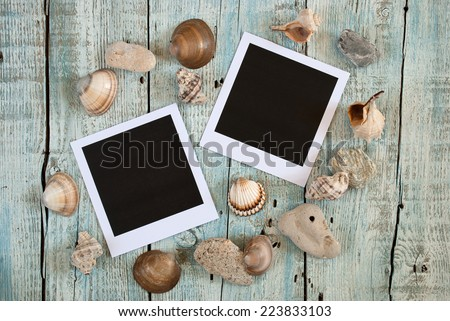 Sea shells and instant photo frames on old wooden table - stock photo