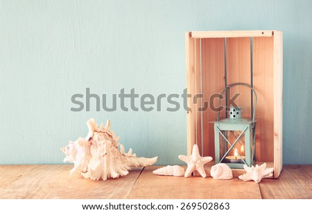 sea shells and lantern on wooden table. vintage filtered image  - stock photo