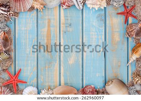 Sea shells frame on vintage shabby wooden board - stock photo