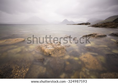sea shore with mountains in the background in isle of skye scotland - stock photo