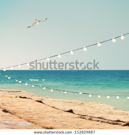 Sea side with party bulbs - stock photo