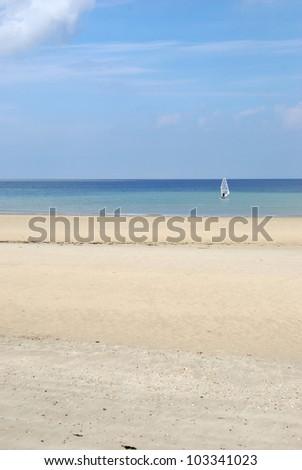 Sea, sky & lone windsurfer - stock photo