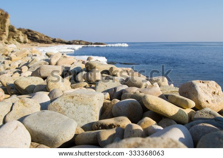 Sea stones on the beach. Icy shore of the sea, the ice Floe. North sea, the cold sea of the North, winter ice, melting of ice. - stock photo