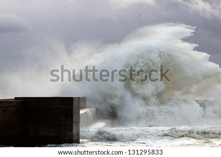 Sea storm with waves crashing against the pier at the mouth of the Douro River on a stormy day - stock photo