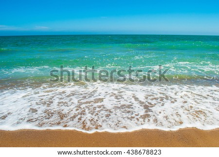 Sea tide and waves on the seashore at the sunny day - stock photo
