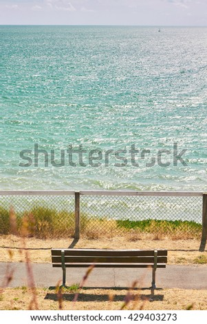 Sea view and an empty bench, seen from the top of a cliff  - stock photo