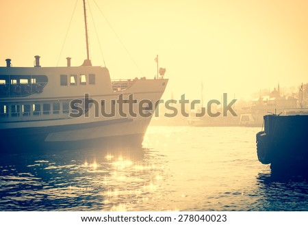 Sea voyage to Bosporus on the ferryboat. Silhouettes of turkish steamboat in Istanbul pier at sunset. Vintage passenger ship in retro style. - stock photo