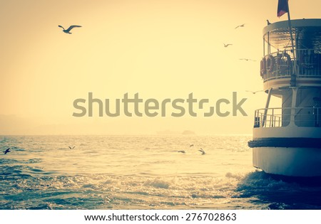 Sea voyage to Bosporus on the ferryboat. Silhouettes of turkish steamboat in Istanbul with seagulls at sunset. Vintage passenger ship with a copy-space for text - travel concept in retro style. - stock photo