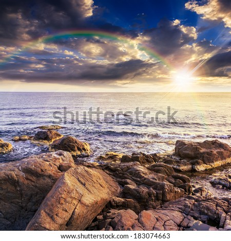 sea wave attacks the boulders and is broken about them at sunset with rainbow - stock photo