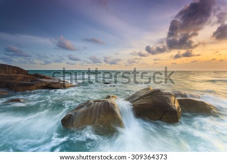 Sea wave hit rock at sunset time. - stock photo
