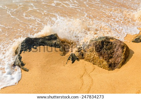 Sea wave impact to sea rock with splashing water shown moving motion - stock photo