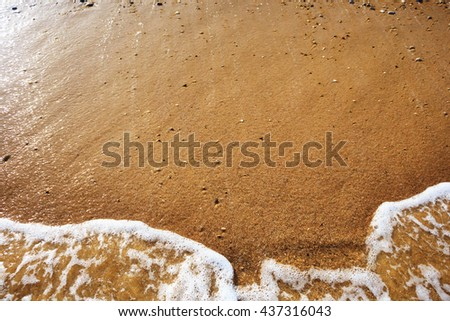 Sea wave on orange pebble sand beach. Abstract background with copy space. - stock photo