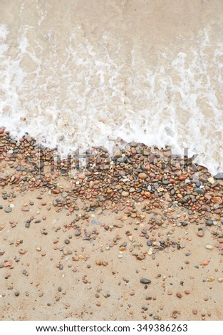 sea wave over the pebbles on the beach, abstract natural background - stock photo