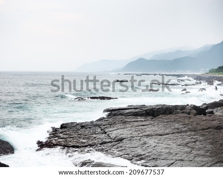 Sea waves crashing against the rocks - stock photo