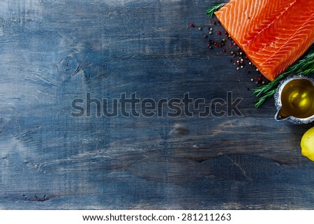 Seafood background. Raw fillet salmon, olive oil, aromatic spices and lemon. Space for text. Vegetarian food, health or cooking concept. Top view. - stock photo