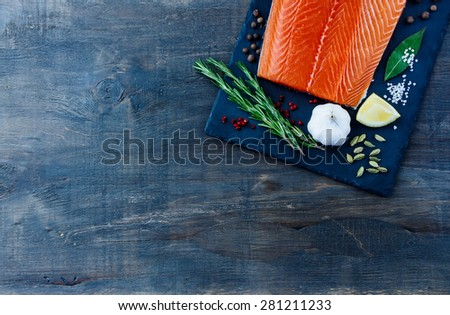 Seafood background with salmon fillet, aromatic spices and lemon on slate texture. Space for text. Vegetarian food, health or cooking concept. Top view. - stock photo