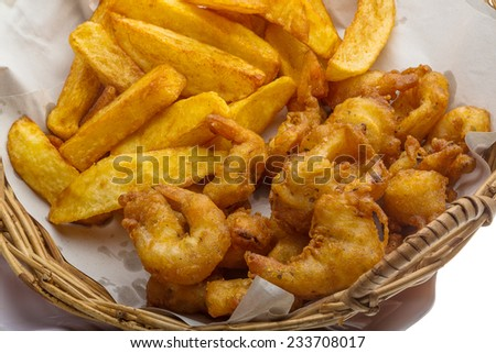 Seafood basket with shrimps, squids and potato - stock photo