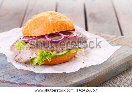 Seafood burger with a freshly baked crusty bun, fillet of fish, onion and lettuce served on a rustic wooden board - stock photo