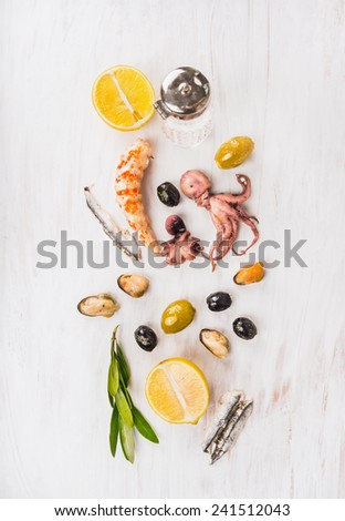 Seafood composing with olives and lemon on white wooden table, top view - stock photo