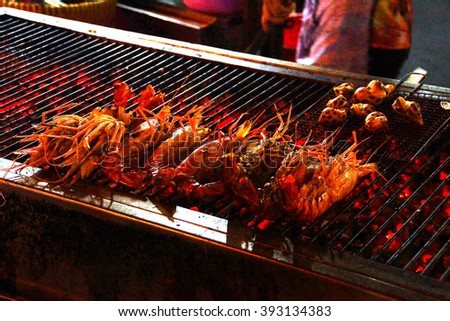 Seafood cooking on flame grill at the night market in Saigon (Ho Chi Minh City),  Vietnam - stock photo