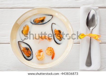 Seafood cream-soup with spoon flat lay. Top view on bowl with seafood cream-soup with shrimps and mussels and spoon on napkin on white wooden background - stock photo