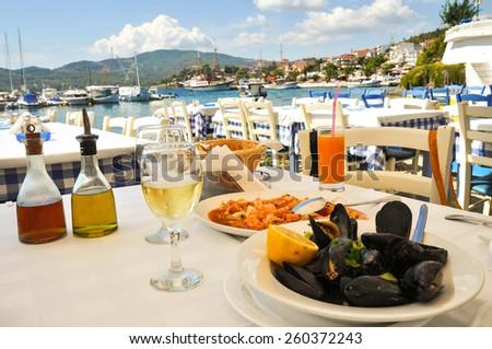 Seafood dinner in a Greece restaurant, Mediterranean sea resort - stock photo