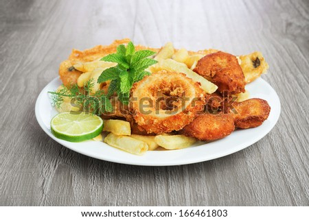 Seafood dish with crumbed fish,calamari,prawn and potato chips on vintage table  - stock photo