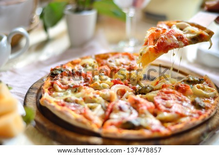 Seafood Italian Pizza slice on wood dish (originality) - stock photo