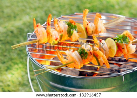 Seafood kebabs with gourmet shelled fresh prawns roasting over the fire on a portable barbecue outside on green grass - stock photo