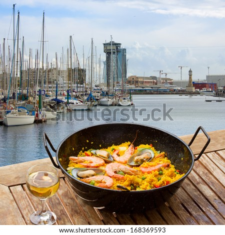 Seafood paella with glass of wine in seaside cafe,port of  Barcelona - stock photo