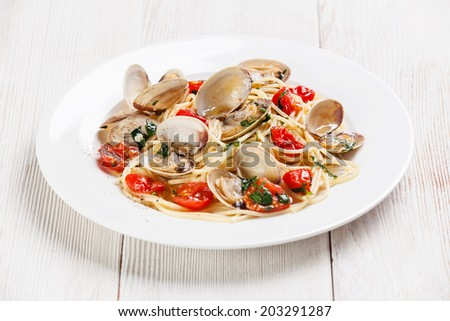 Seafood pasta with clams in tomato sauce Spaghetti alle Vongole on white wooden background - stock photo