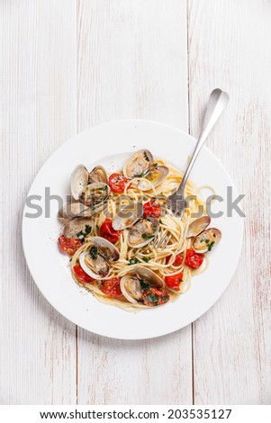 Seafood pasta with clams in tomato sauce Spaghetti Vongole on white wooden background - stock photo