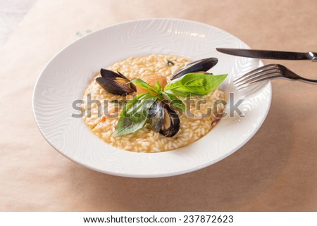 Seafood risotto in plate on paper background - stock photo