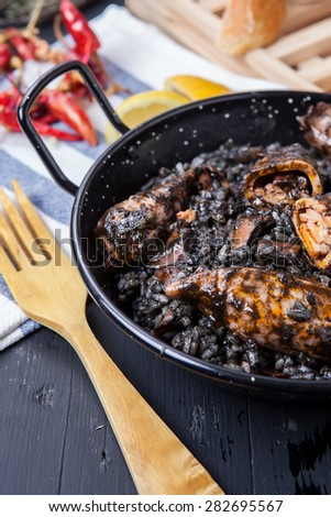seafood risotto with black calamari ink on pot - stock photo