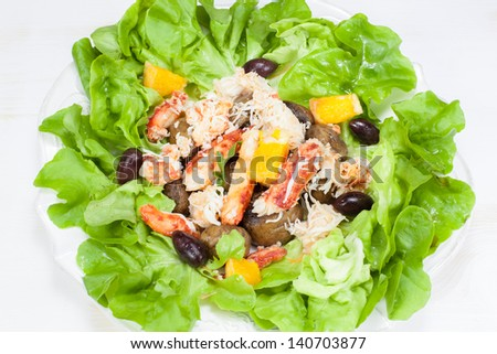 Seafood salad.    Salad of crab, shrimp, mixed greens and olive. Viewed from above. - stock photo