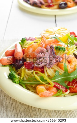 Seafood spaghetti pasta dish with octopus, shrimps, cherry tomatoes and olives - stock photo
