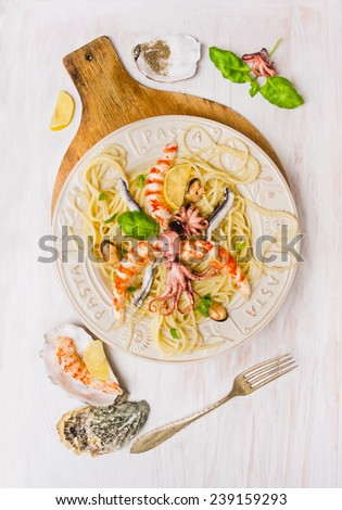 seafood spaghetti with  mussel,  anchovy, baby octopus and  big shrimp, on white wooden background, top view - stock photo