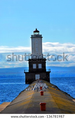 Seagulls and one eagle rests on the pier leading to the Keweenaw Waterway Lighthouse. - stock photo