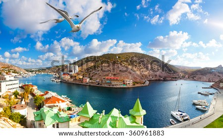 Seagulls fly over Balaklava Bay to the sunny summer day - stock photo