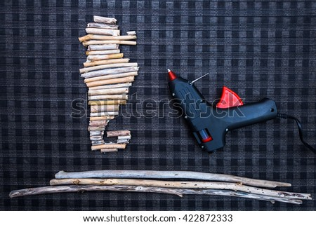 Seahorse shape made from driftwood as home decoration object with glue pistol - stock photo