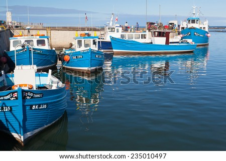 Seahouses,England -July 20,2012: Typical blue fishing boats in Seahouses harbor - stock photo