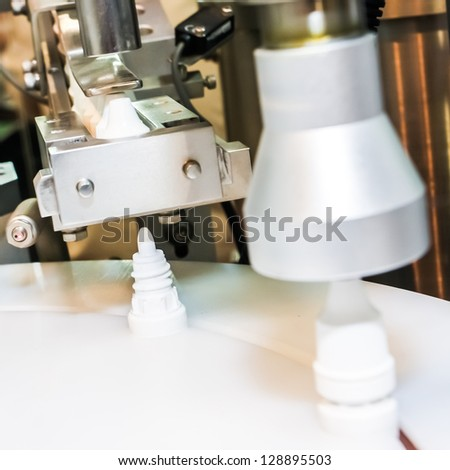 Seal the cap or lid in the pharmaceutical factory - stock photo