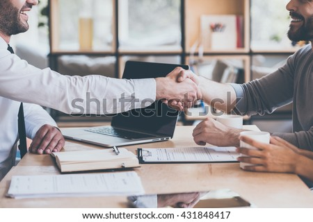 Sealing a deal. Side view close-up of two young man shaking hands while sitting at the wooden desk - stock photo