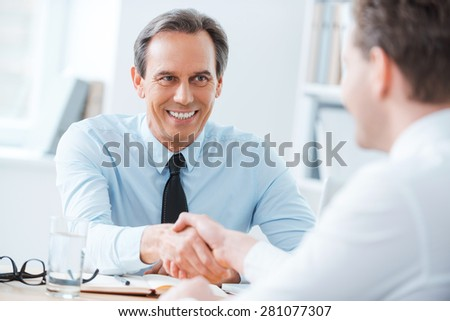 Sealing a deal. Two business people shaking hands while sitting at the working place - stock photo