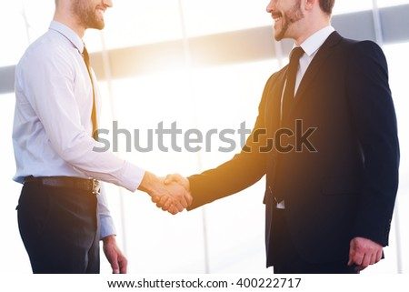Sealing good deal. Two cheerful business men shaking hands and smiling while standing indoors - stock photo