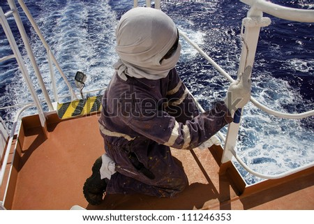 Seaman at work. Painting with the roller. - stock photo