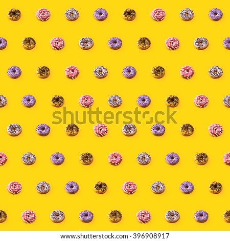 Seamless pattern with colorful glazed donuts on yellow background. 4 different kinds of frosting - pink with marshmallow, yellow with chocolate, white and purple with sweet topping. - stock photo