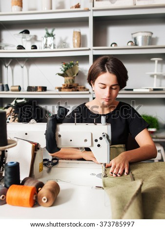 seamstress making clothes. Workplace of tailor - sewing machine, rolls of  thread, fabric, scissors. - stock photo
