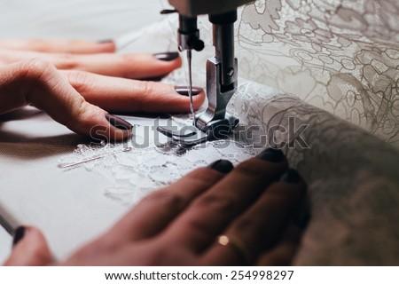 Seamstress , sewing lace wedding dress on the sewing machine . - stock photo